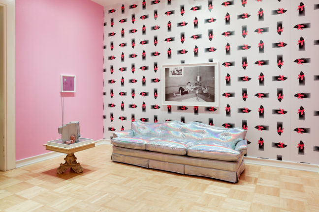 <p>Sadie Barnette, <i>Room to Live</i>, 2019. Mixed media installation, holographic vinyl sofa, metal flake TV, archival inkjet prints, metal flake security cameras. Courtesy of the artist. Installation view of <i>In Plain Sight</i>, 2019, Henry Art Gallery, University of Washington, Seattle. Photo: Mark Woods.</p>