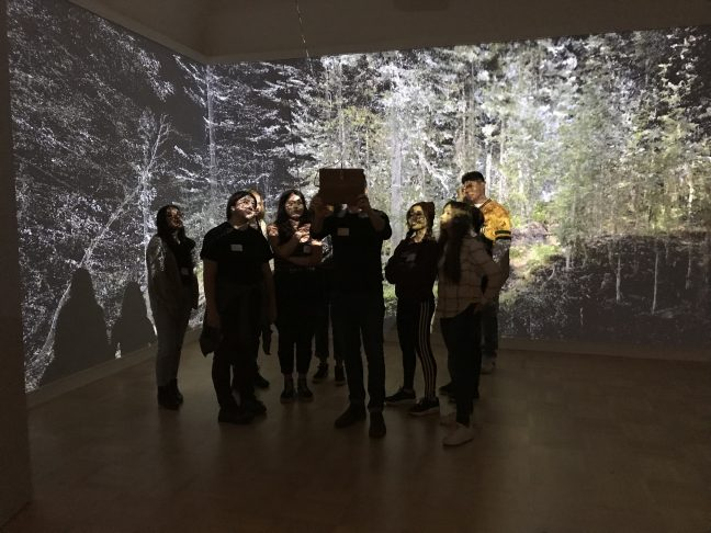 <p>Exhibiting artist Abe Avnisan shows members of the Henry Teen Art Collective his installation, <em>Sin Sol, Forest Memory</em>, a collaboration with artist micha cárdenas<em>.</em> Photo: Katrina Herzog.<br /></p>