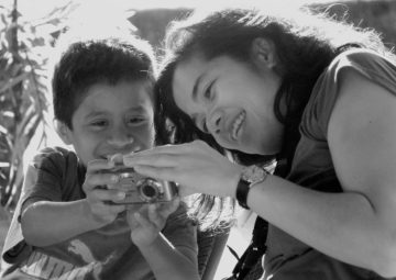 <p>Carina A. del Rosario teaching a young boy. Image credit: Shelly Schmidt. </p>